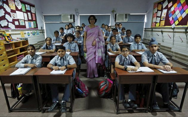 Teacher Archana Shori poses for a picture with 7th-grade level students inside their classroom at Rukmini...