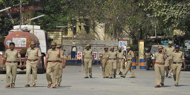Indian police personnel patrol at the entrance to Gulf Oil Corporation Limited company (Explosives Division)...