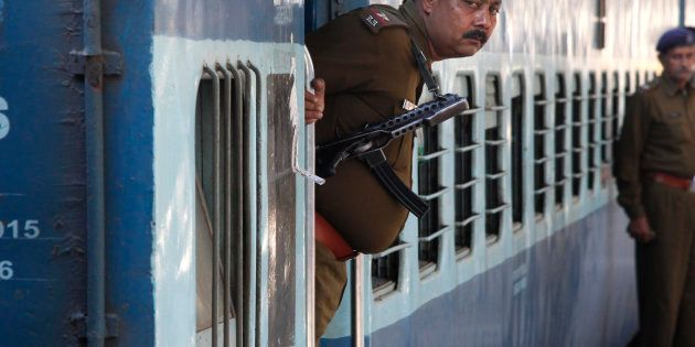A Railway Police personnel peeps out from the door of a special passenger train at a railway station...