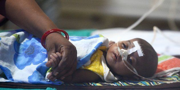 An Indian woman holds her child's hand at the encephalitis ward of the the Baba Raghav Das Hospital in...