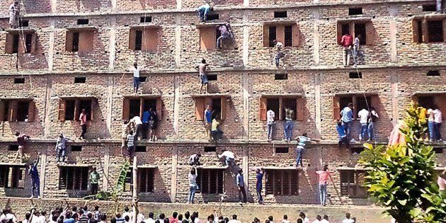 In this photograph taken on March 19, 2015, Indian relatives of students taking school exams climb the...