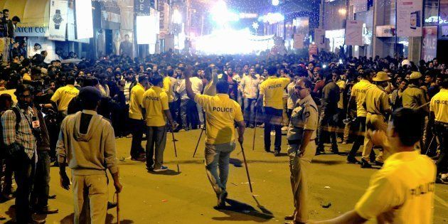 Indian police personnel holding 'lathi' sticks try to manage crowds during New Year's Eve celebrations...