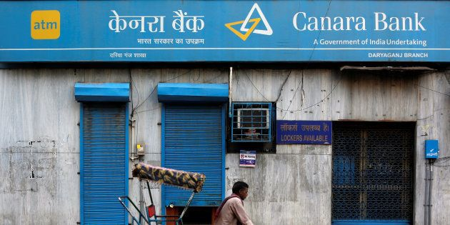 A rickshaw puller passes the Canara Bank branch in the old quarters of Delhi, India, September 6, 2017....