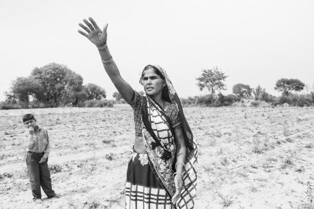 Madhubala, Sheetal's mother, gestures as she stands in the middle of the family land. All the crops have...