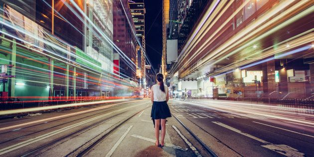 Young woman is lost in metropolitan city at night, Hong