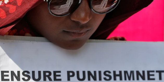 A woman holds a placard at a protest against the rape of an eight-year-old girl, in Kathua, near Jammu...