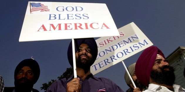 Sikh men carry patriotic placards at a community service to remember victims of terrorist attacks, October...