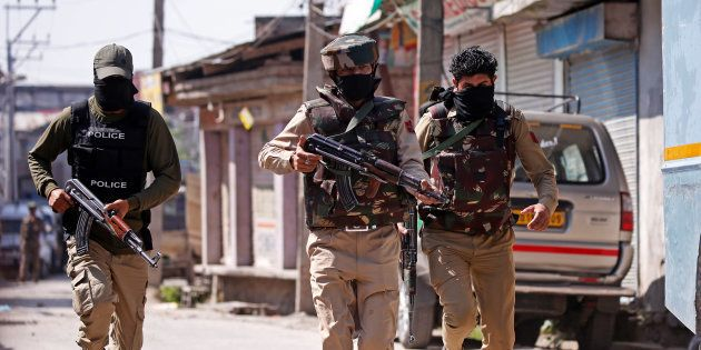 Indian army soldiers patrol a street near a site of a gunbattle between Indian security forces and suspected...