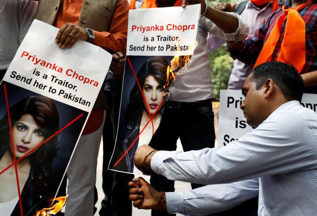 Supporters of Hindu Sena, a right wing Hindu group, burn posters of Priyanka Chopra during a protest...