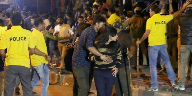 In this photograph taken on January 1, 2017, an Indian man helps a woman (C) leave as police personnel...