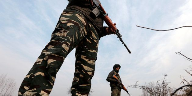 Policemen stand guard outside the Central Reserve Police Force (CRPF) training centre during a gunbattle...