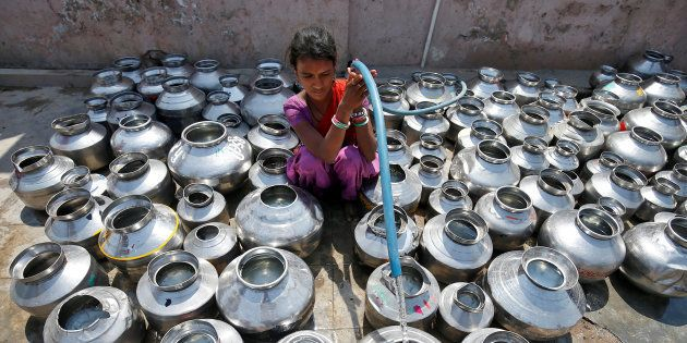 A girl fills metal pitchers with drinking water from a tubewell outside a temple in Ahmedabad, India...