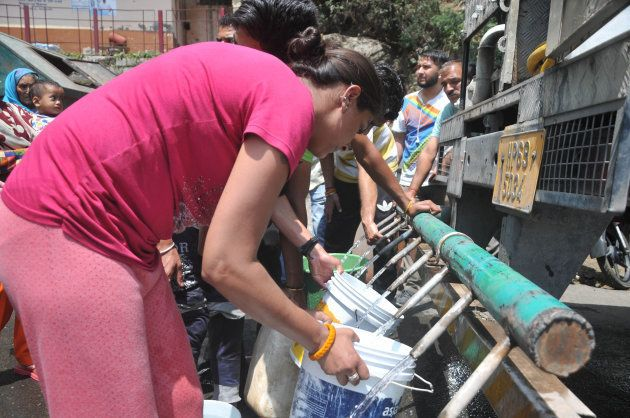 Indian residents gather to collect drinking water with buckets from a water tanker following water shortages...