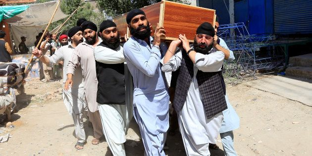 Afghan Sikh men carry the coffin of one of the victims of yesterday's blast in Jalalabad city, Afghanistan...