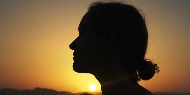 Silhouette of a young woman at sunset. Image used for representational purposes