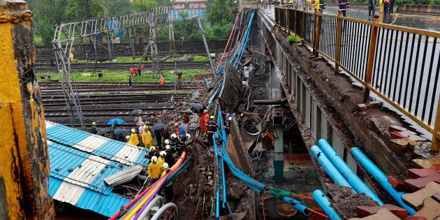 Rescue workers seen working at the site of an overbridge that collapsed over the railway tracks after...