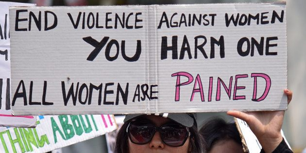 A woman holds a placard during a protest against the rape of an eight-year-old girl in Kathua, near Jammu,...