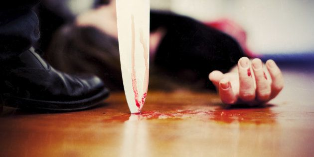 'Close up on a bloody knife planted on a wooden floor, a killing