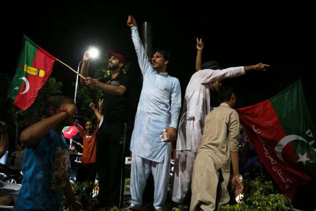 Supporters of Imran Khan, chairman of the Pakistan Tehreek-e-Insaf (PTI), political party celebrate during...