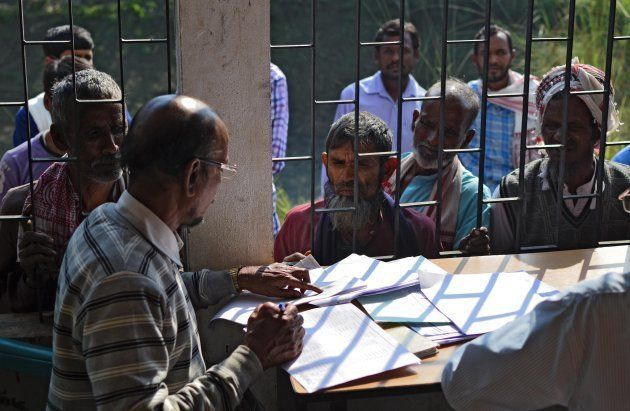 People wait to check their names on the first draft of the National Register of Citizens (NRC) at Goroimari...