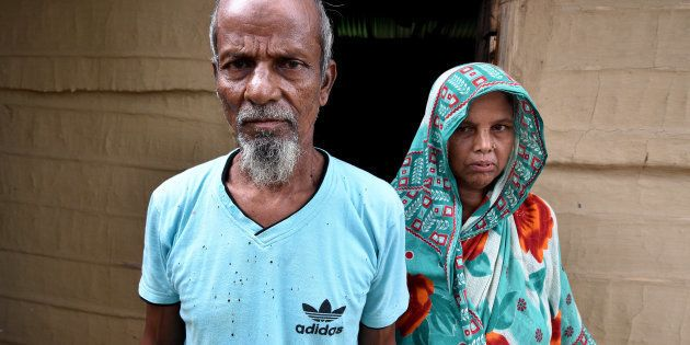 Abdul Suban, a farmer, and his wife pose for a photograph outside their home in Nellie village, in Morigaon...