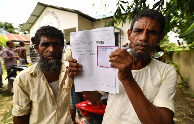 A resident holds documents on his way to check their names on the final list of National Register of...