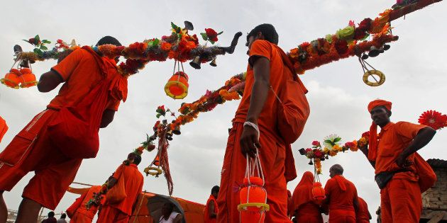 Kanwariyas or devotees of Hindu Lord Shiva arrive to fill their pots with holy water from the river Ganges,...