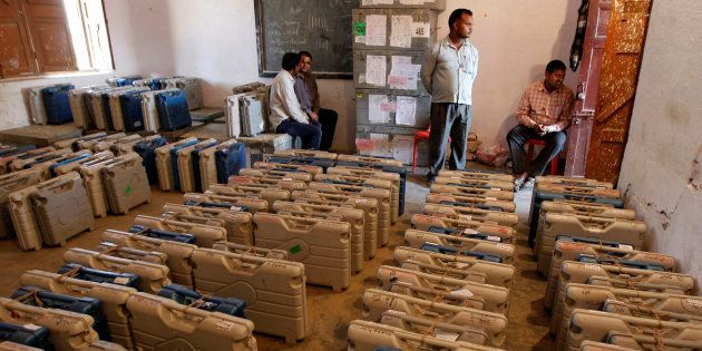 Members of the election staff sit in a room filled with electronic voting machines (EVM) at a distribution...