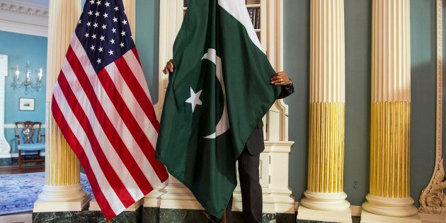 A State Department contractor adjust a Pakistan national flag before a meeting between U.S. Secretary...