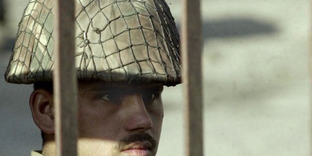 File photo of an Indian Border Security Force (BSF) soldier peers out from behind the main gate to the...