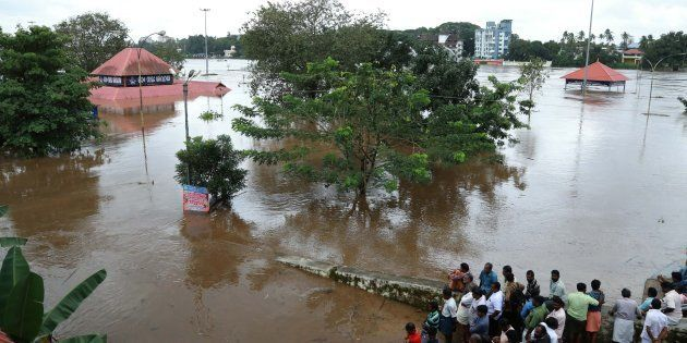 Indian residents look at the Shiva Temple submerged after the release of water from Idamalayar dam following...