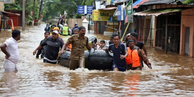 Rescuers evacuate people from a flooded area to a safer place in Aluva in Kerala on