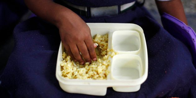 File photos of a schoolgirl eating her free mid-day meal, distributed by a government-run primary school,...