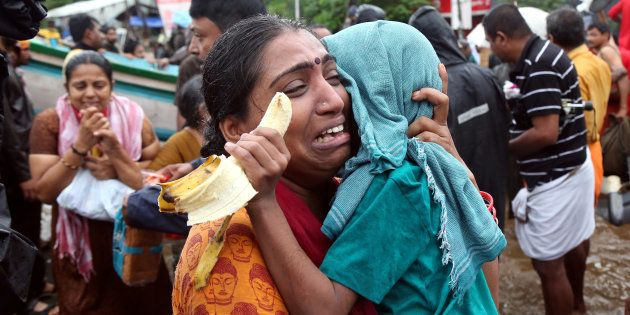 A woman cries as she holds her son after they were evacuated from a flooded area in Aluva in the southern...