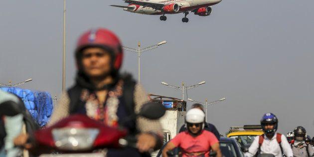 An Air India Ltd. aircraft passes over traffic as it prepares to land at Chhatrapati Shivaji International...
