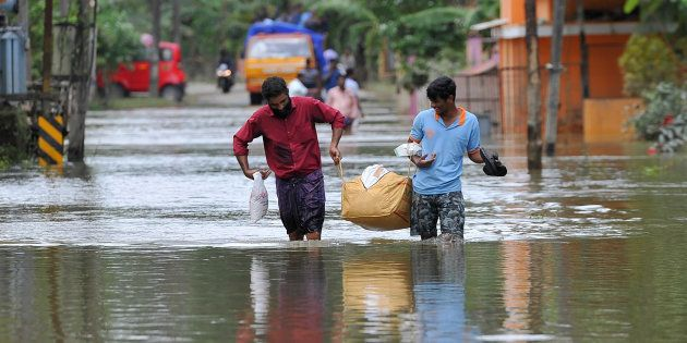People carry food and water aid distributed to those stranded by floods in Pandanad in Alappuzha District...