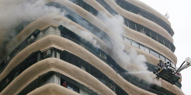 Residents wait to be rescued as firefighters try to extinguish a fire at a residential building in Mumbai,...
