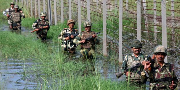 Indian Border Security Force (BSF) soldiers patrol the fenced border with