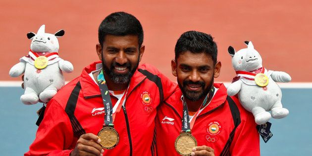 Gold medallists Rohan Manchanda Bopanna and Divij Sharan of India celebrate with their medals and plush...