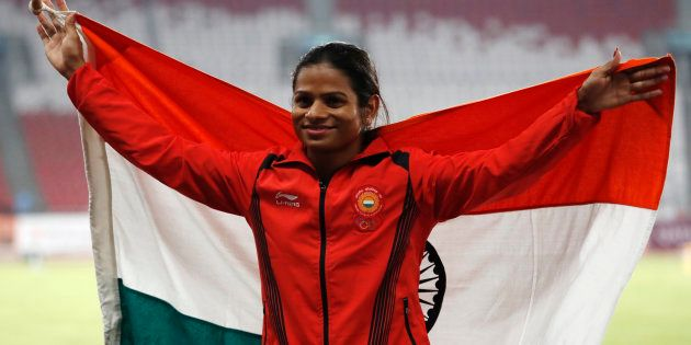 Silver medallist Dutee Chand poses with her national flag during the medal ceremony. REUTERS/Darren