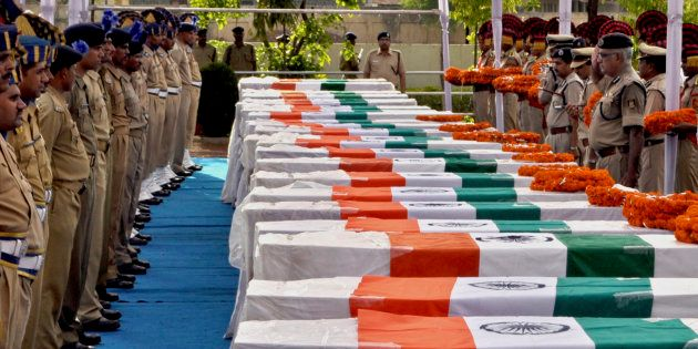 Central Reserve Police Force (CRPF) personnel pay their last respects near the coffins of policemen who...