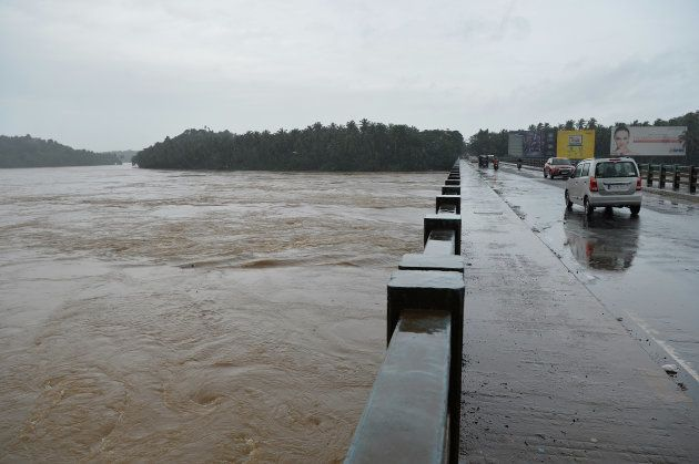 Vehicles drive on a bridge over the overflowing Chaliyar river in Kozhikode, Kerala, on 17