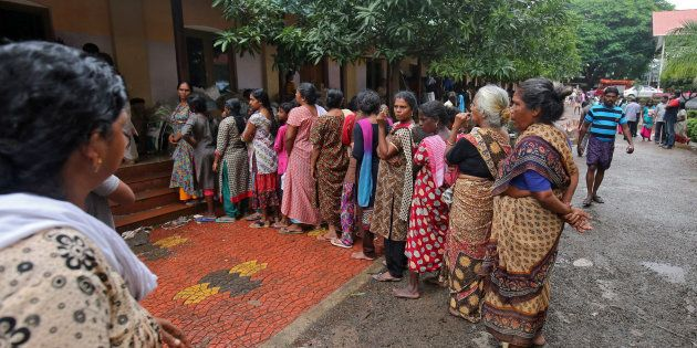 Flood-affected women wait to receive relief material at a camp in Chengannur in Kerala on 20
