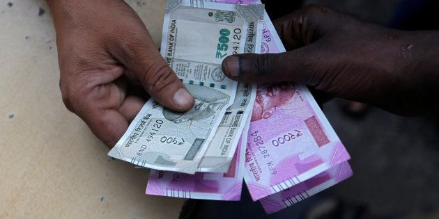 A customer hands Indian currency notes to an attendant at a fuel station in Mumbai, India, August 13,...