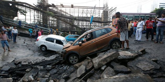 People stand next to the wreckage of vehicles at the site of a bridge that collapsed in Kolkata, India...