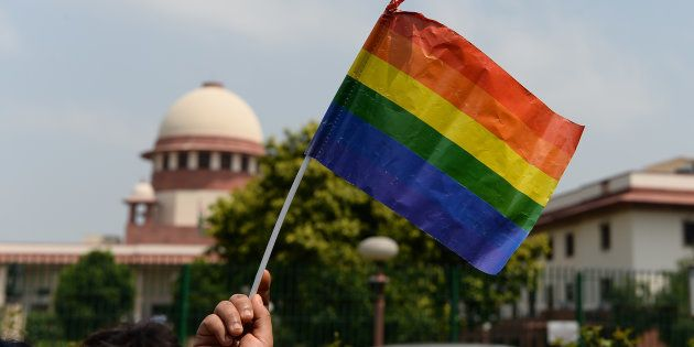 A member of the LGBT community waves a flag outside the Supreme Court building as crowds gathered to...