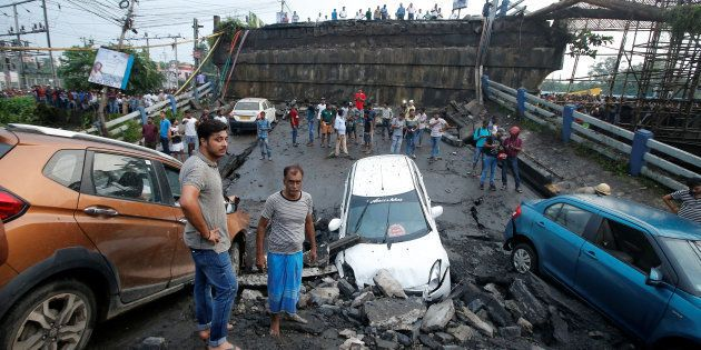 People stand next to the wreckage of vehicles near the Majerhat bridge, which collapsed on