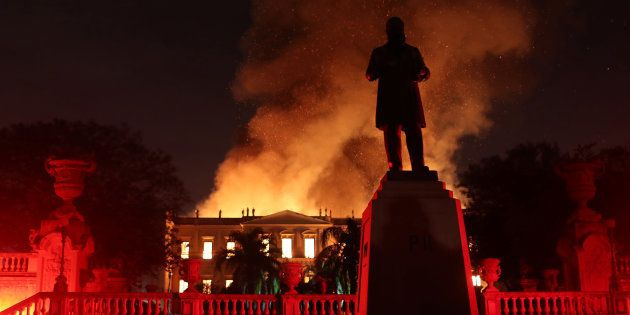 Flames spread behind the Statue of D Pedro II at the Quinta da Boa Vista National