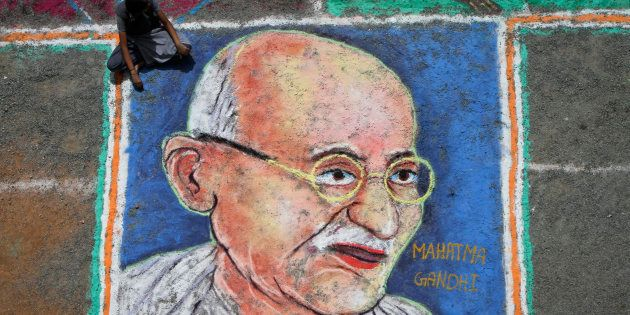 A student sits next to a painting of Mahatma Gandhi as part of Independence Day