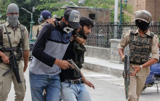 A policeman dressed as a stone pelter arrests a Kashmiri protester during clashes in Srinagar on 7